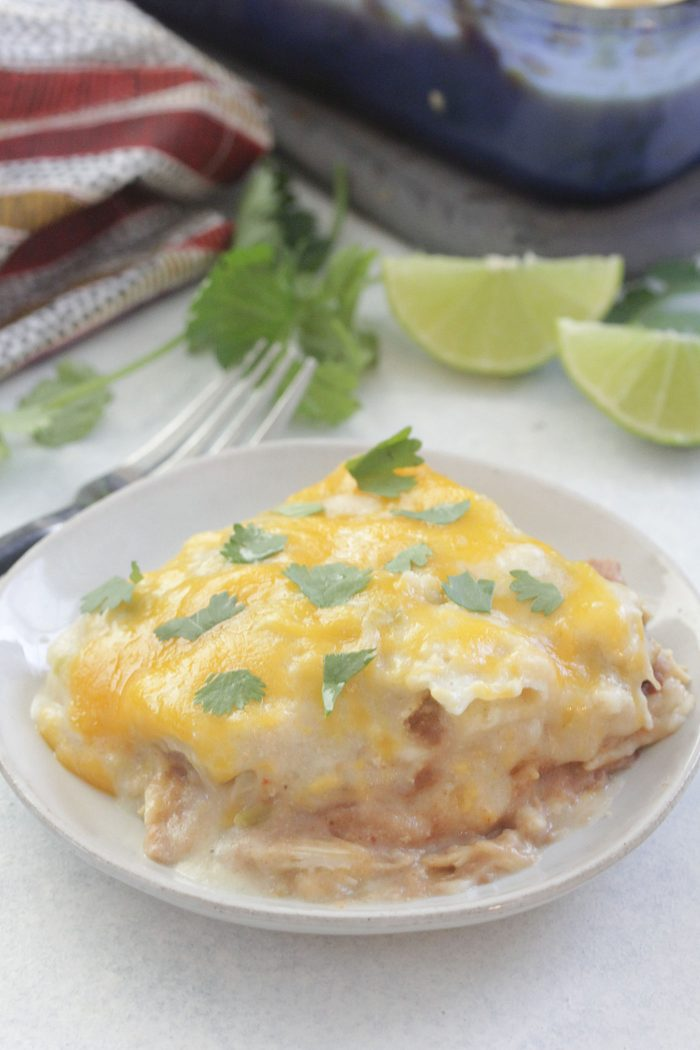 White Chicken Enchilada Casserole on a white plate with lime wedges