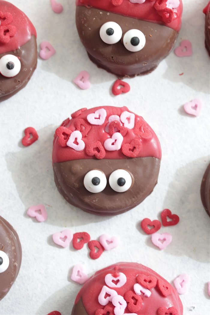 Love Bug Cookies on a white board with heart sprinkles overhead shot