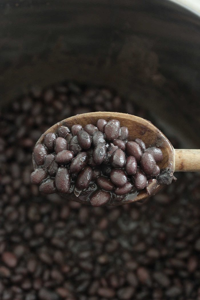 Instant Pot Black Beans scooped on a wooden spoon
