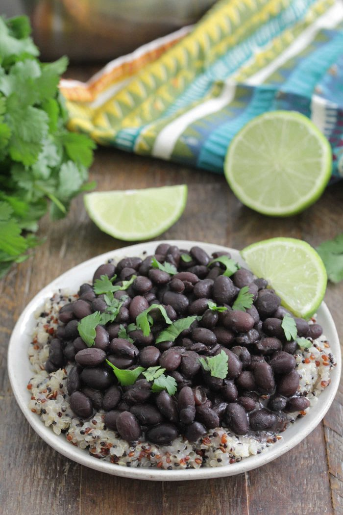 Instant Pot Black Beans on top of quinoa with fresh lime slices and cilantro