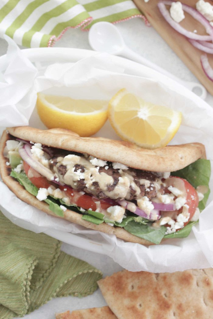 Overhead shot of Greek Burgers in a pita with feta, lemon, tomato in a white basket