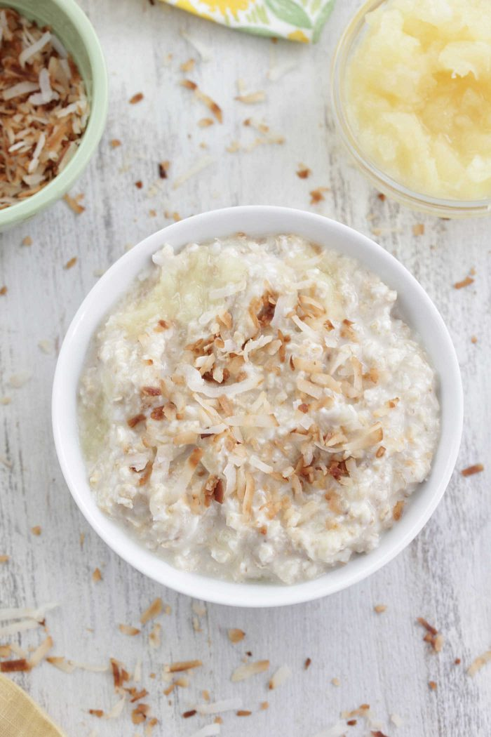 Piña colada overnight oats overhead shot in a white bowl with toasted coconut on top