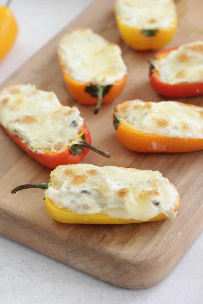 Creamy Artichoke Stuffed Peppers on a wooden serving board