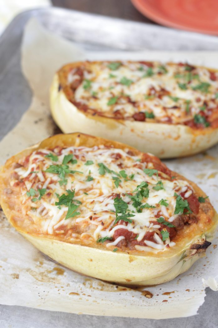 Lasagna-Stuffed Spaghetti Squash on a baking sheet with parchment paper