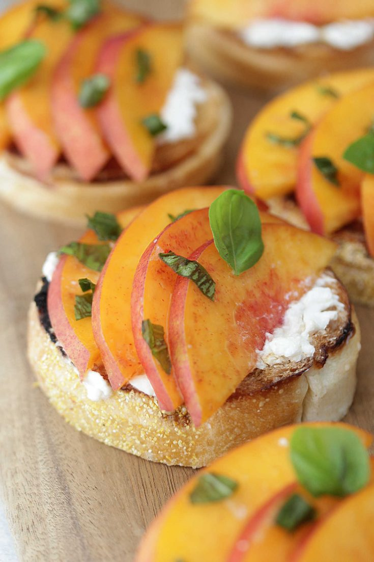Peach Burrata Toasts on a wooden board topped with chopped basil