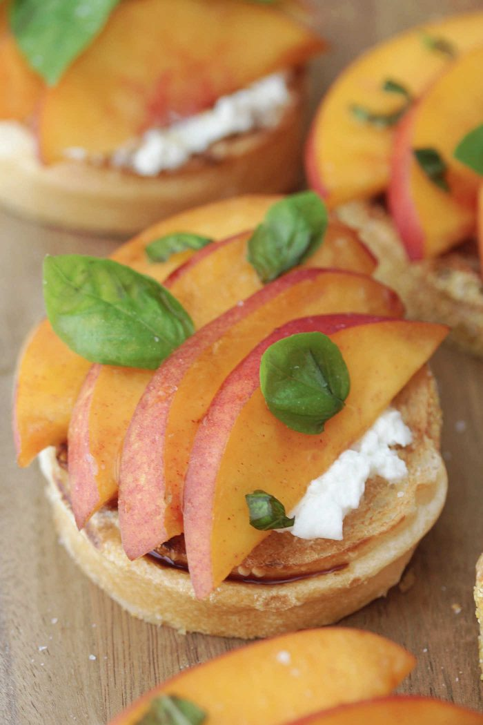 Close-up shot of sliced peaches on toasts with burrata cheese and basil