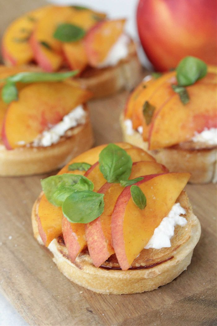 Peach burrata toasts on a wooden board with fresh basil leaves and a peach