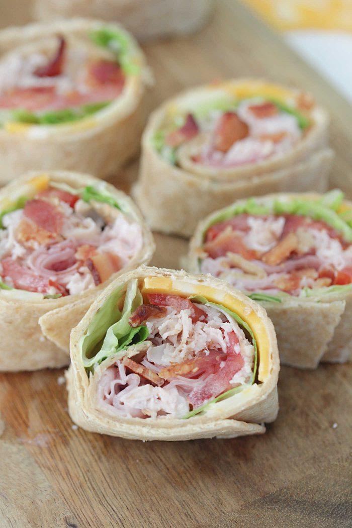 Ham & Turkey Club Pinwheels arranged on a wooden serving board