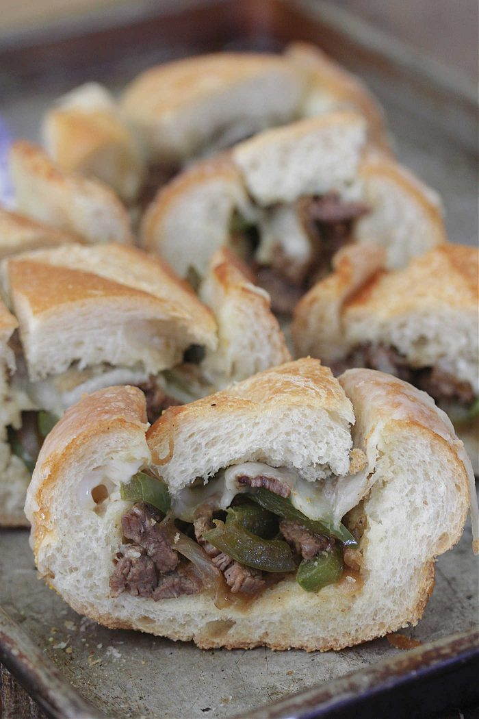 Philly Cheesesteak Stuffed French Bread slices on a baking sheet
