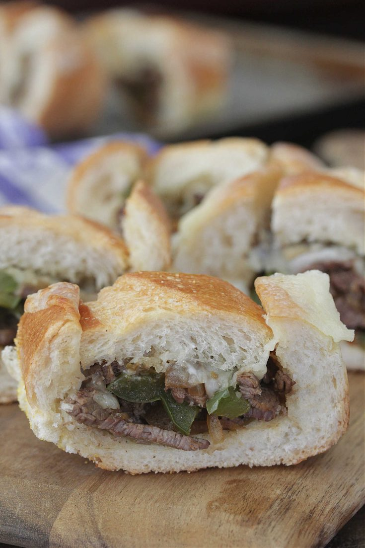 Philly Cheesesteak Stuffed French Bread on a wooden board
